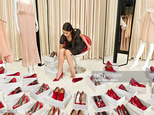 young lady trying on a pair of shiny red high heel