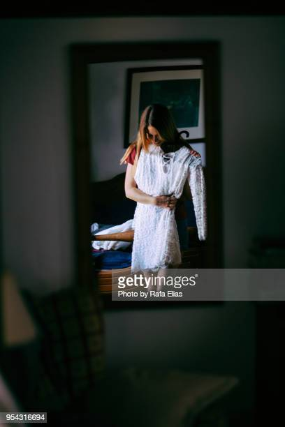 young lady trying on white dress in front of mirror - dress stock pictures, royalty-free photos & images