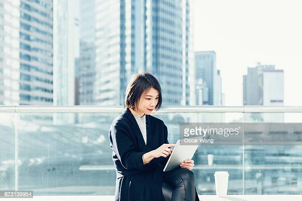 Young lady using digital tablet outdoor against cityscape