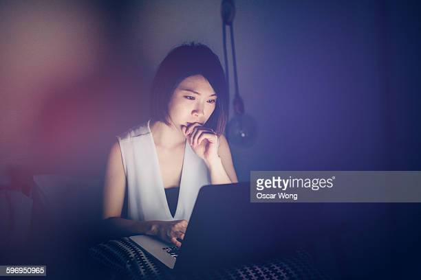 Young lady using laptop in bed
