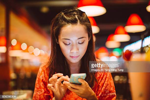 Young lady using smarphone in restaurant