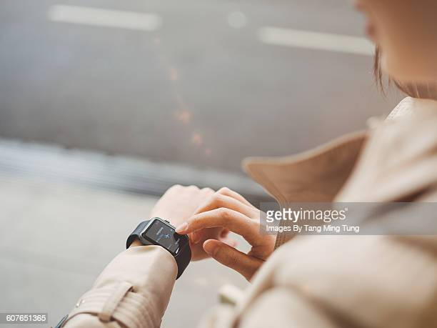 Young lady using smart watch on the street