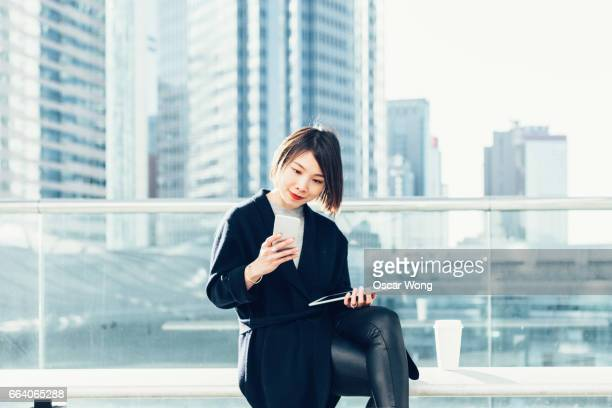 Young lady using smartphone and digital tablet in balcony against city background