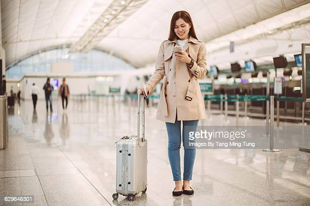 Young lady using smartphone at airport