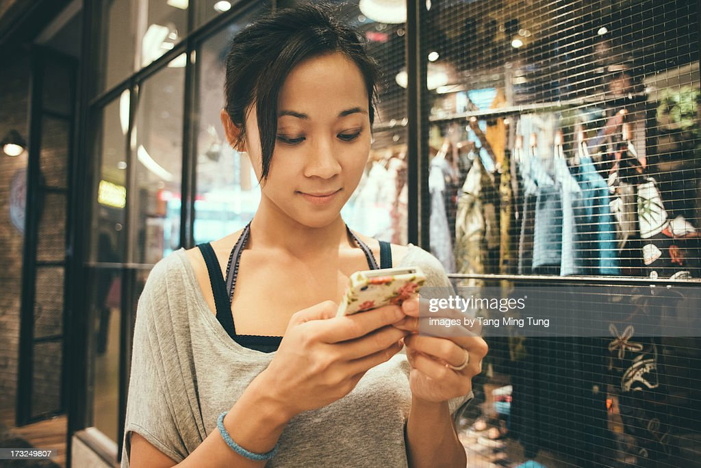 Young lady using smartphone in boutique. : Stock Photo