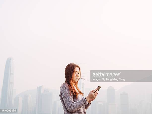 Young lady using smartphone in promenade