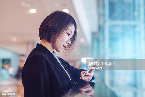 Young lady using smartphone in shopping mall