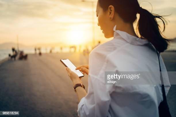 Young lady using smartphone while having a relaxing walk by the pier afterwork at sunset