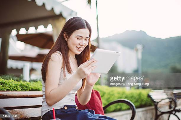 Young lady using tablet on bench at promenade