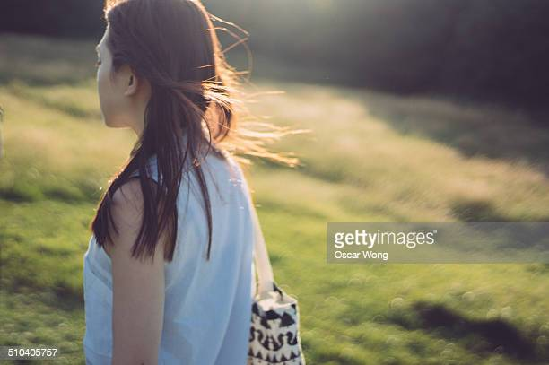 a young lady walking in a park alone - woman carrying tote bag stock photos and pictures