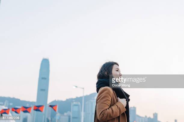 Young lady walking in city, against Hong Kong cityscape