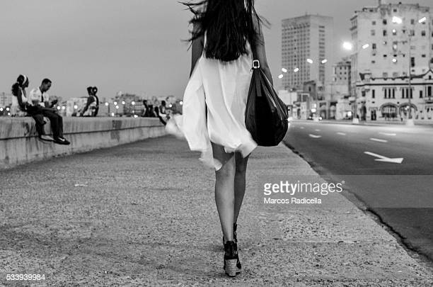 young lady walking in the malecón, havana, cuba - radicella stock photos and pictures