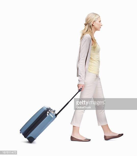 Young lady walking with her luggage