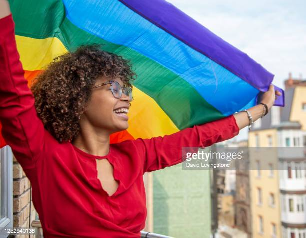 young lady waving a gay pride flag in support of gay pride - pride stock pictures, royalty-free photos & images