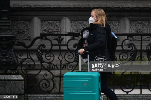 Young lady wearing a face mask carrying a monkey staffed toy and pushing a luggage seen in Dublin city center during Level 5 Covid-19 lockdown. On...