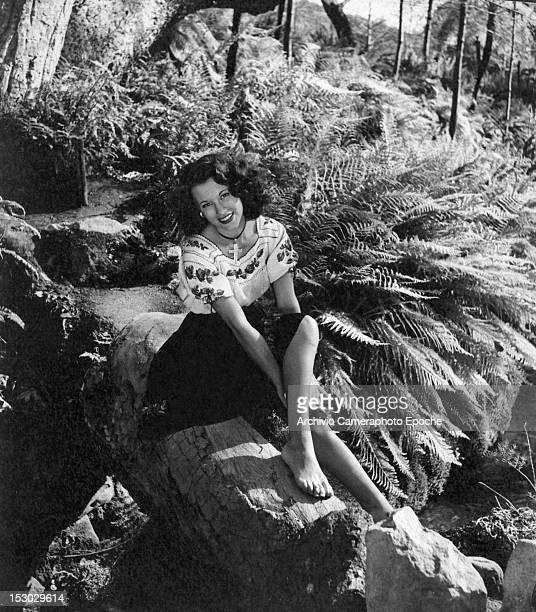 A young lady wearing a fancy shirt and a cross necklace portrayed while posing in a hood glade surrounded by ferns circa 1948
