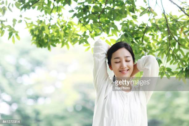young lady who is closing his eyes and enjoying rest in the park