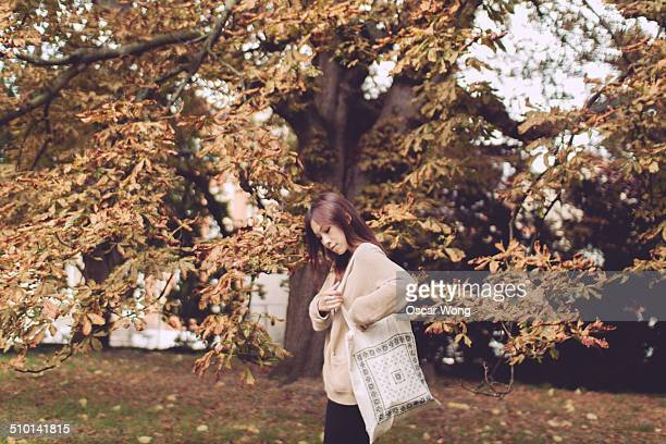 Young lady with a tote bag in a park