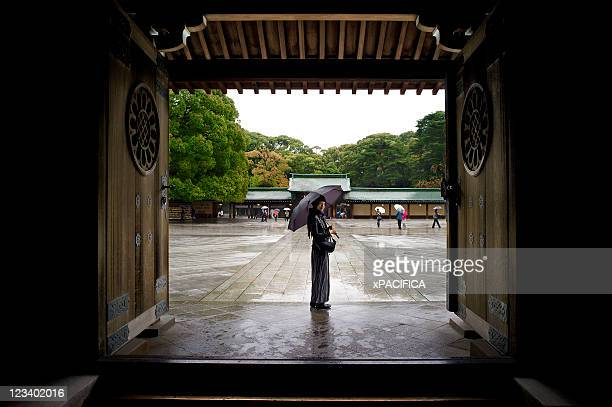 a young lady with an umbrella standing in a temple - 神社 ストックフォトと画像