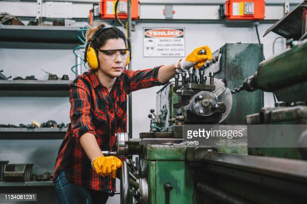 Young lathe worker woman working with milling machine in factory