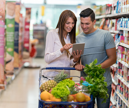 Young latin american couple looking at shopping list on a mobile app at the supermarket - gettyimageskorea