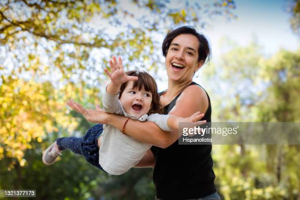young latin american happy mom playing airplane with her daughter at the park both looking excited while mom faces camera smiling - innocence stock pictures, royalty-free photos & images