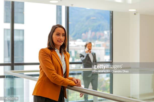 young latin american lady dressed in business casual clothes waits for a colleague to arrive in the lobby area on the floor of her office building - coat stock pictures, royalty-free photos & images