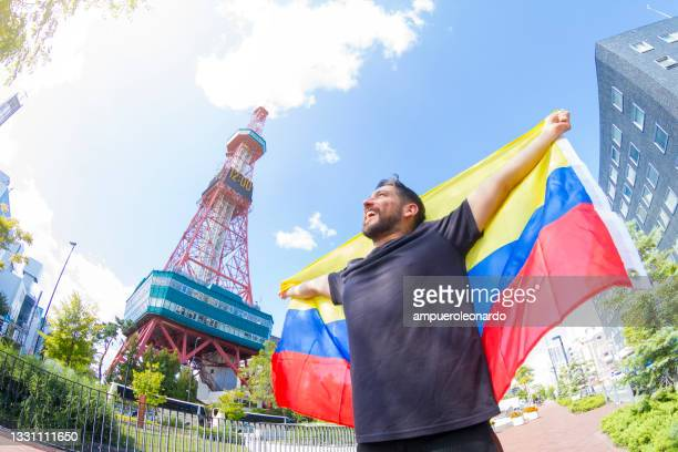 jovem fã de mochileiros latinos comemorando um prêmio em um evento esportivo internacional, em frente à torre sapporo em sapporo, hokkaido, japão - medalhista - fotografias e filmes do acervo