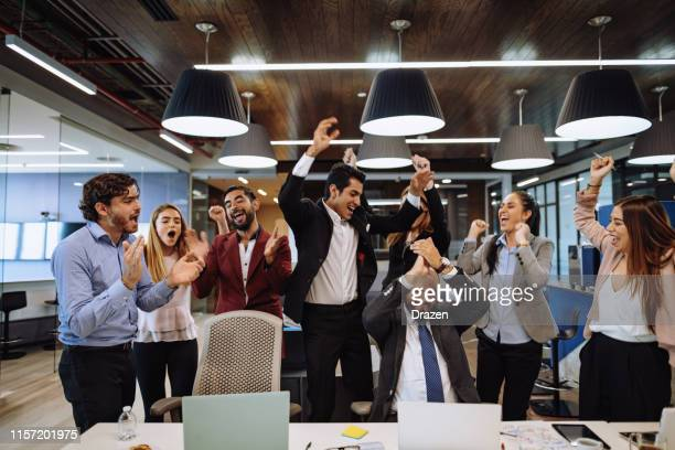 young latin business people celebrate successful fundraising for start-up. - fundraising stock pictures, royalty-free photos & images
