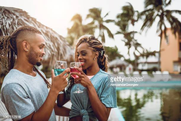Young Latin Couple Making Cocktails Toast In A Tourist Resort
