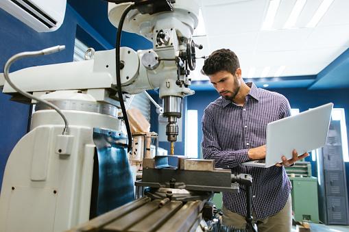 Young latin engineer calibrating drill 1057719100
