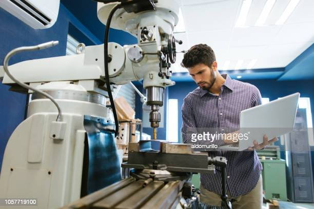 young latin engineer calibrating drill - engineering stock pictures, royalty-free photos & images