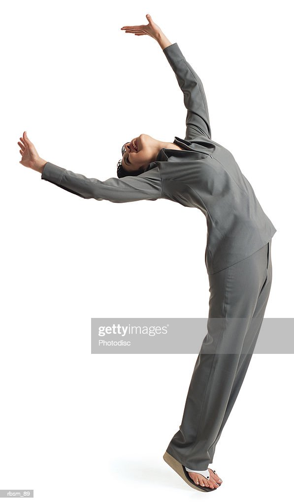 young latin female dancer grey suit leans forward tilts her head back throws her arms into the air : Foto de stock