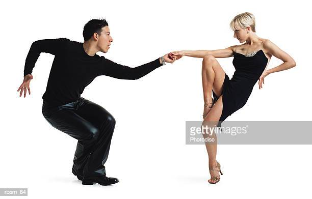young latin male and young caucasian blonde female dance partners tango dressed in black
