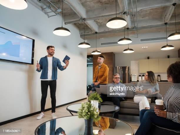 コワーキングスペースでプレゼンテーションを行う若いラテン人男性 - セールストーク ストックフォトと画像