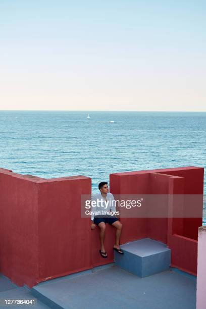young latin man meditative in a red building, sea on background - europa meridionale foto e immagini stock