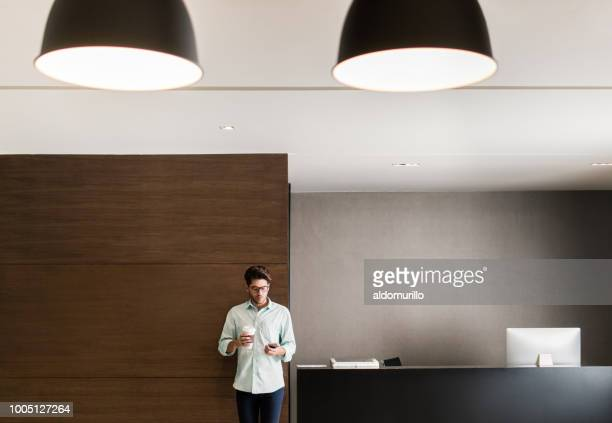 Young latin man standing with coffee and mobile phone