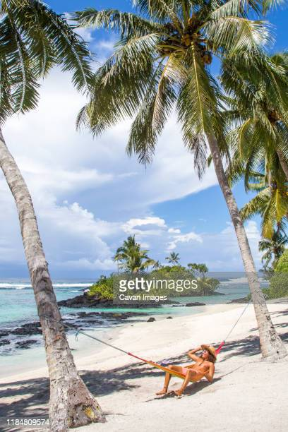 young latin man, with curly hair, wearing hat, on hammock at beach - samoa stock pictures, royalty-free photos & images