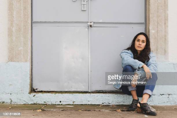 a young latin, mexican woman sitting in front of a metal door in mexico city, mexico - jeansstoff stock-fotos und bilder