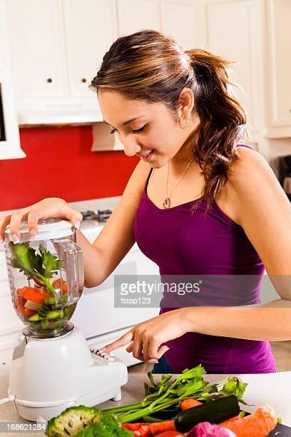 Jeune femme latine, mélange de légumes. Smoothies équilibrés. Cuisine Home