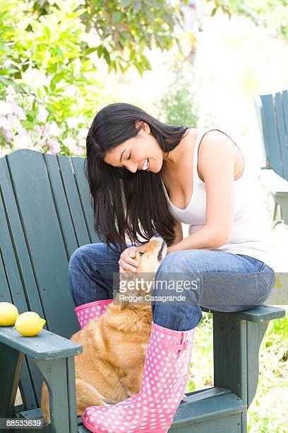 young Latin woman in galoshes with Corgi dog