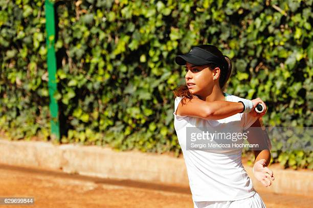 A young latin woman plays tennis in Mexico City