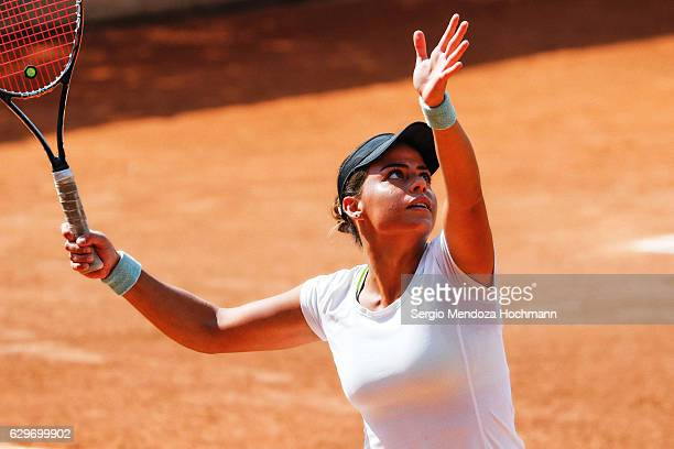 A young latin woman plays tennis in Mexico City - receiving a high ball