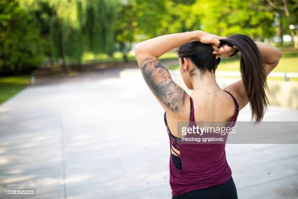 young latin woman tying her hair before exercising outdoors - hair back stock pictures, royalty-free photos & images