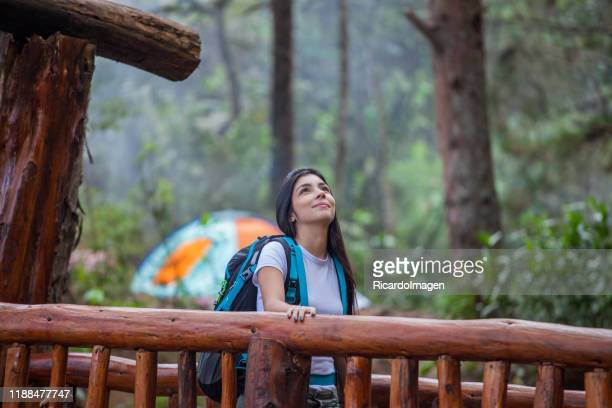 young latin woman walks by wooden bridge of the natural park of the city of medellin - medellin colombia stock pictures, royalty-free photos & images