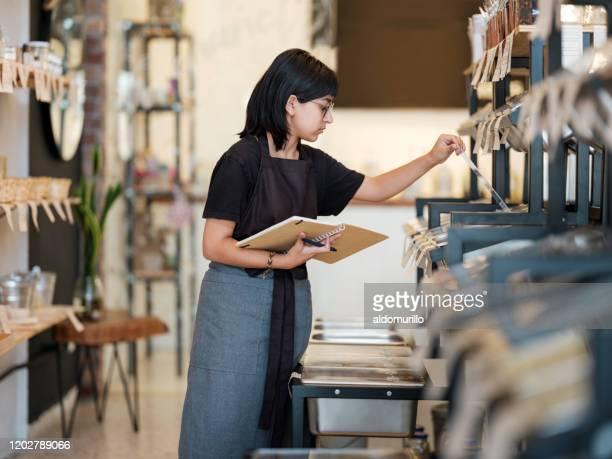 Jonge Latijnse vrouw die in organische opslag werkt en producten controleert