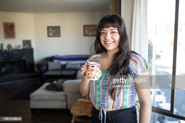 young latina stands alone in her living room, wearing woven ethnic blouse, smiling, holding a floral pottery mug - mexican culture stock pictures, royalty-free photos & images