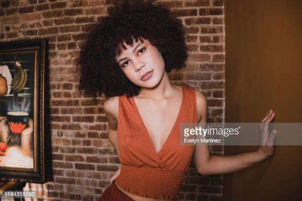 Young Latina wearing orange top and orange bottom standing with one hand on her waist, one hand on the wall. Girl has a short afro. Background is an exposed brick wall and a painting.