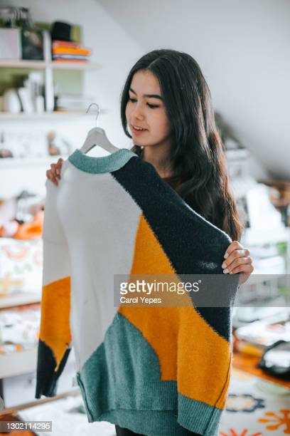 young latina woman choosing a sweater from her closet - clothing stock pictures, royalty-free photos & images