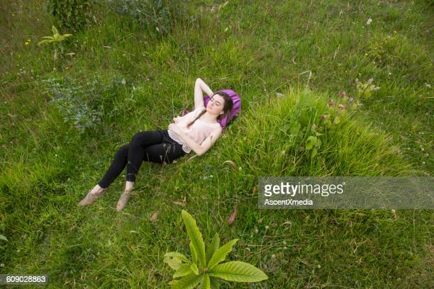 Young Latina woman relaxes in meadow, on backpack